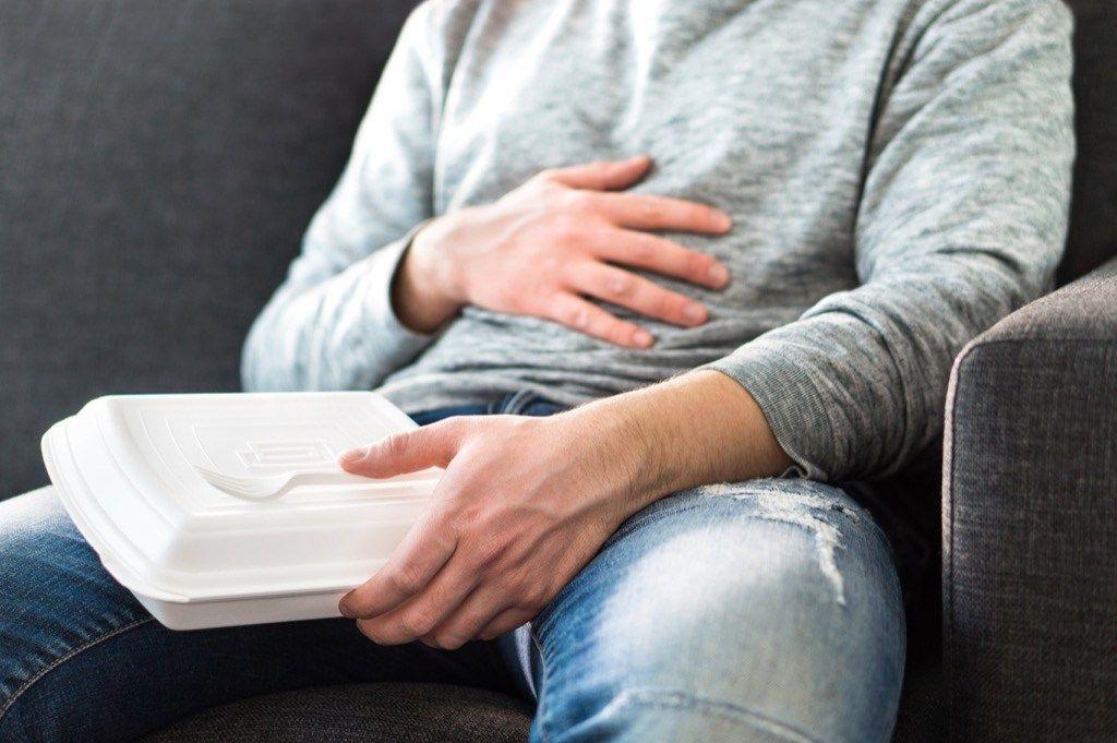 Homem com mão sobre a barriga segurando marmita descartável | Por que sentimos sono depois de comer?
