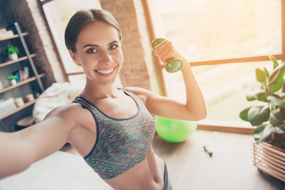 Mulher tirando selfie segurando halter fazendo exercício em casa | Como escolher um bom colchonete para academia?