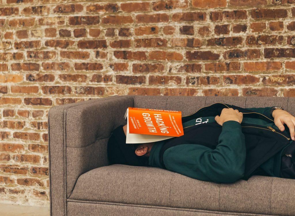 Pessoa com sono excessivo dormindo com o livro no rosto